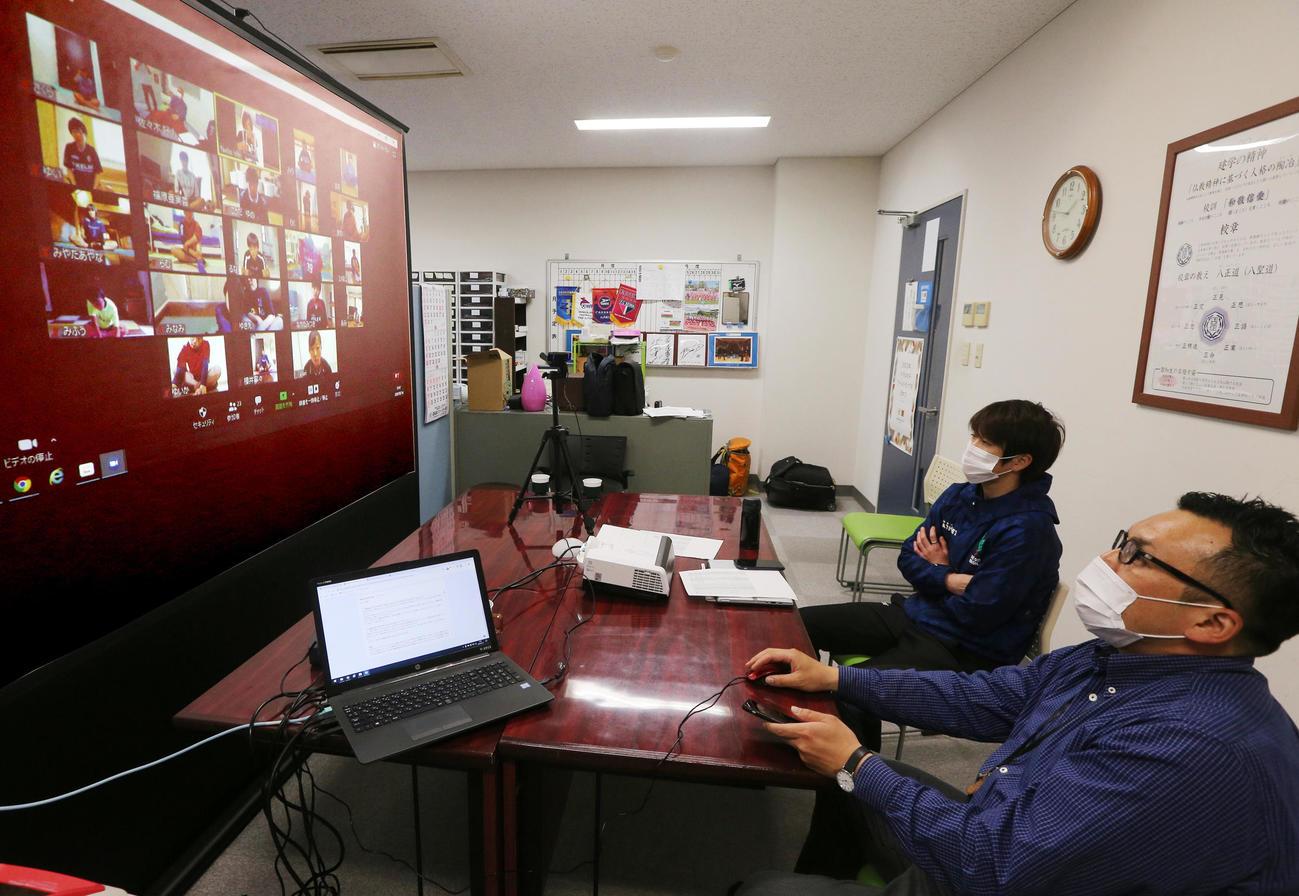 オンラインでの練習を見つめる手前から聖和学園・佐々木顧問、曽山監督(撮影・野上伸悟)