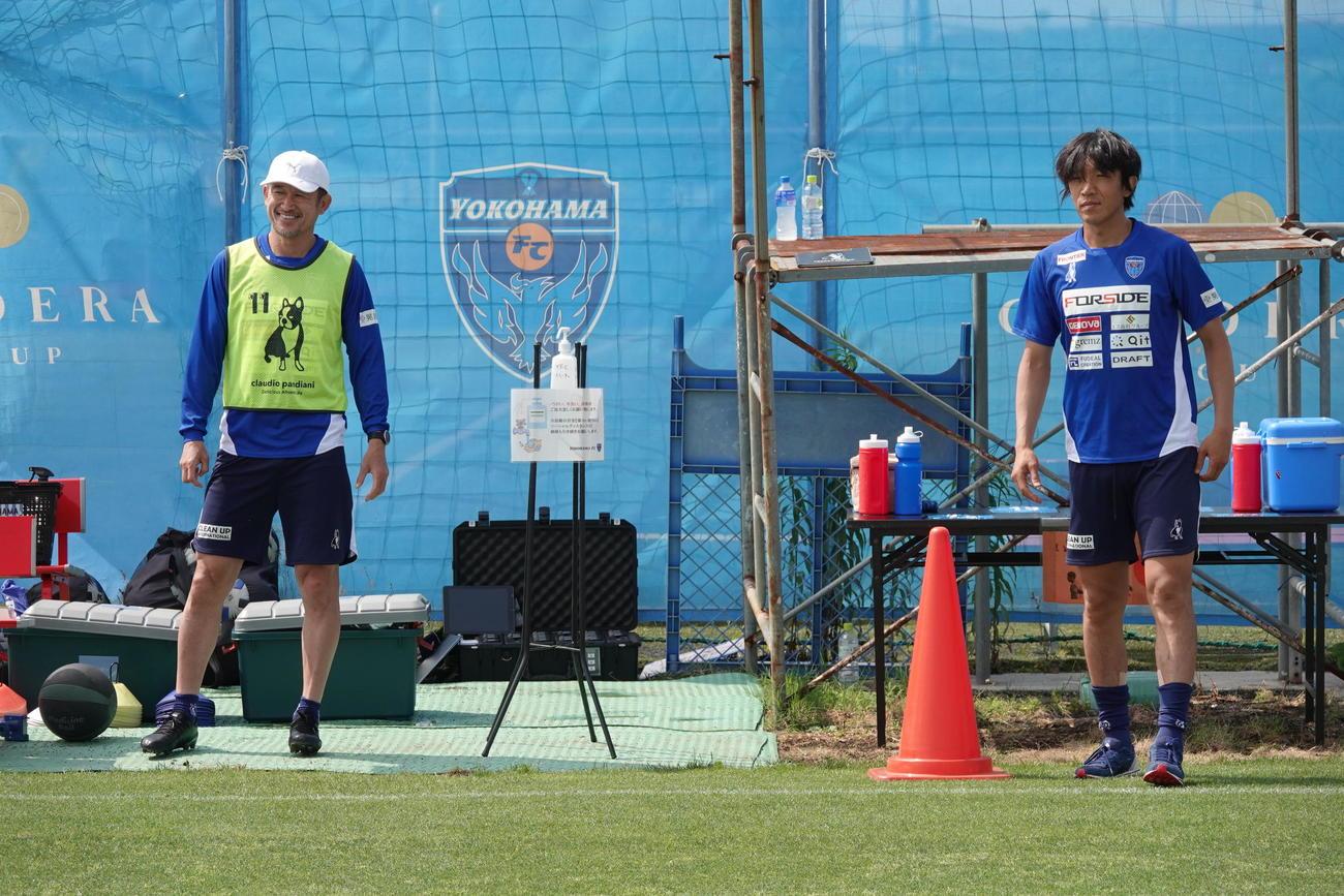 チーム練習が再開になり、ソーシャルディスタンスを取りトレーニングに参加したFWカズ(左)とMF中村(C)YOKOHAMA FC