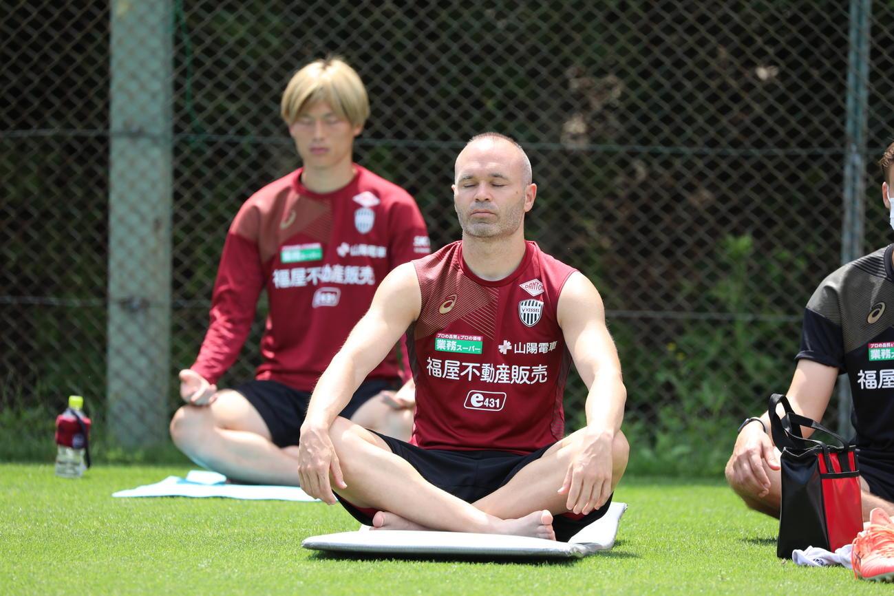 座禅を組む神戸MFイニエスタ。後方はFW古橋(C)VISSEL KOBE