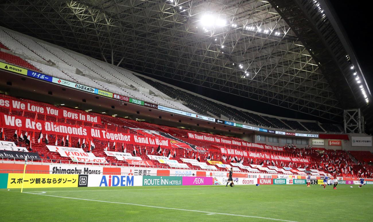浦和対横浜 無観客での再開となった埼玉スタジアムでは、赤、白、黒のビニールをシートにかけ文字を作り、様々な旗を掲げた(撮影・浅見桂子)