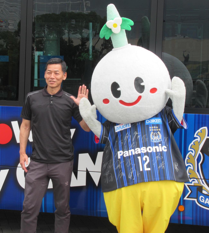 阪急バスの特別車両の前でG大阪小野社長(左)と大阪・吹田市のマスコット「すいたん」