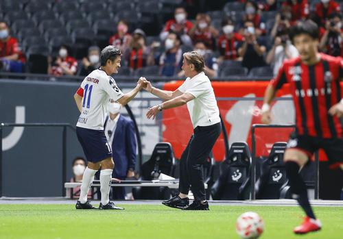 札幌―横浜FC 試合前、札幌・ペトロビッチ監督とタッチを交わす横浜FC・三浦(左)(共同)