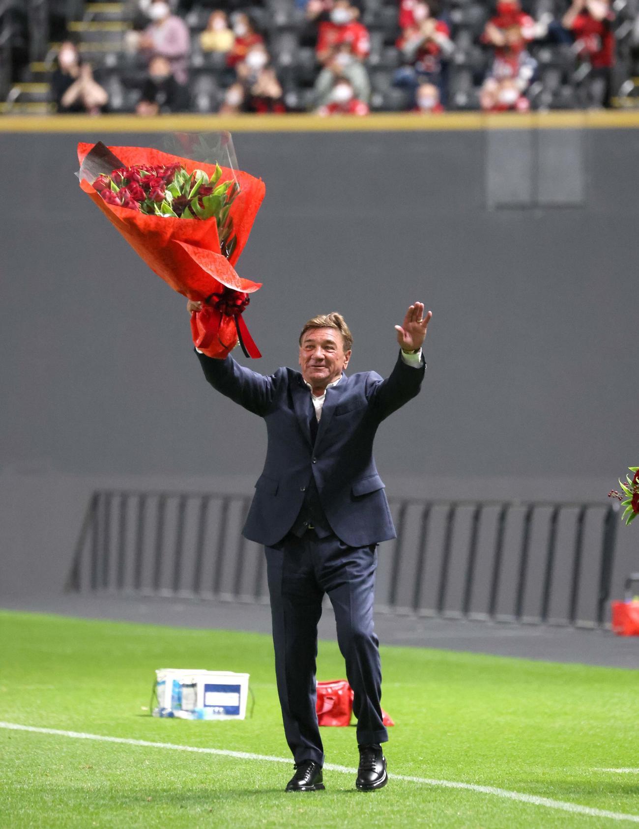 札幌対横浜FC 試合後、スタンドに向かって花束を掲げるペトロビッチ監督(撮影・黒川智章)