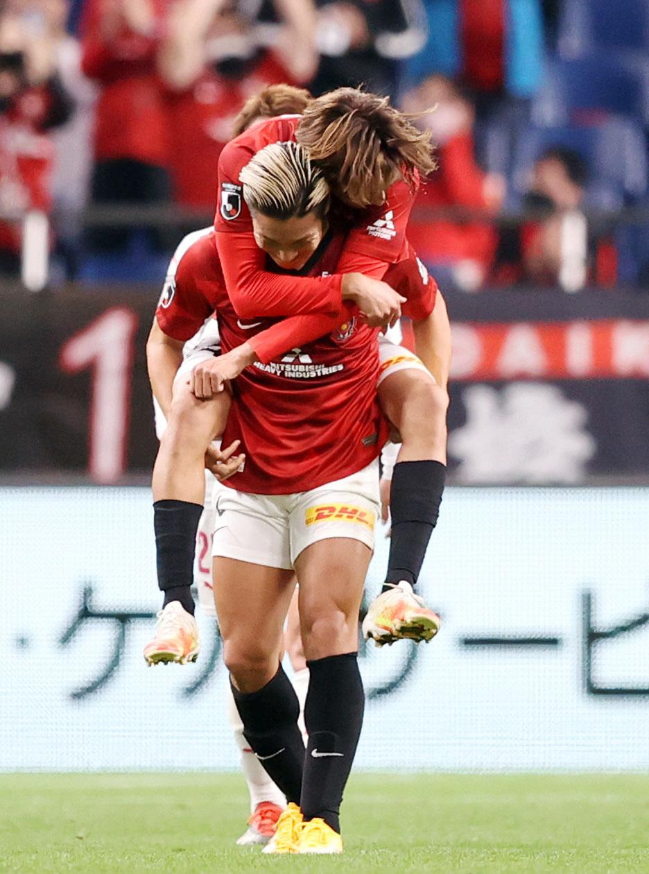 浦和対C大阪 前半、ゴールを決め、浦和MF汰木(後方)に乗っかられ、そのままおんぶするDF山中(撮影・狩俣裕三)