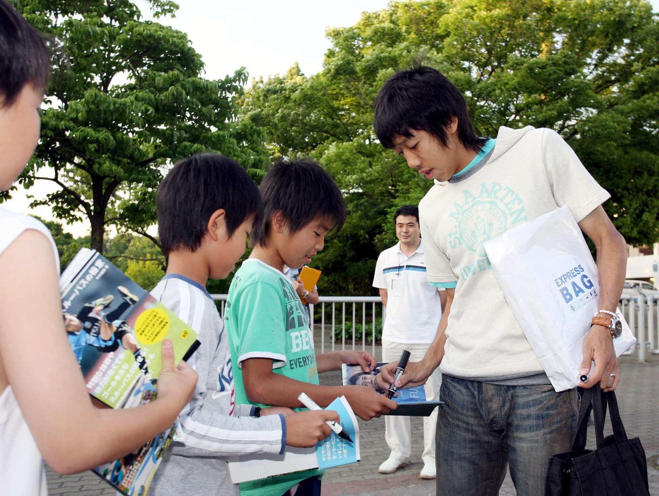 子供たちにサインする川崎FのMF中村憲剛(09年5月18日)