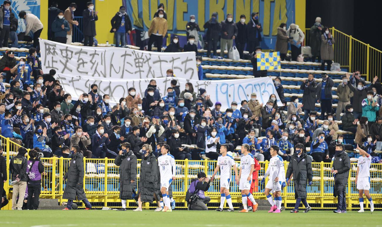 柏対大分 戦力外が発表された選手へのメッセージを記した横断幕をサポーターが掲げる中、試合後にあいさつする大分の選手たち(撮影・野上伸悟)