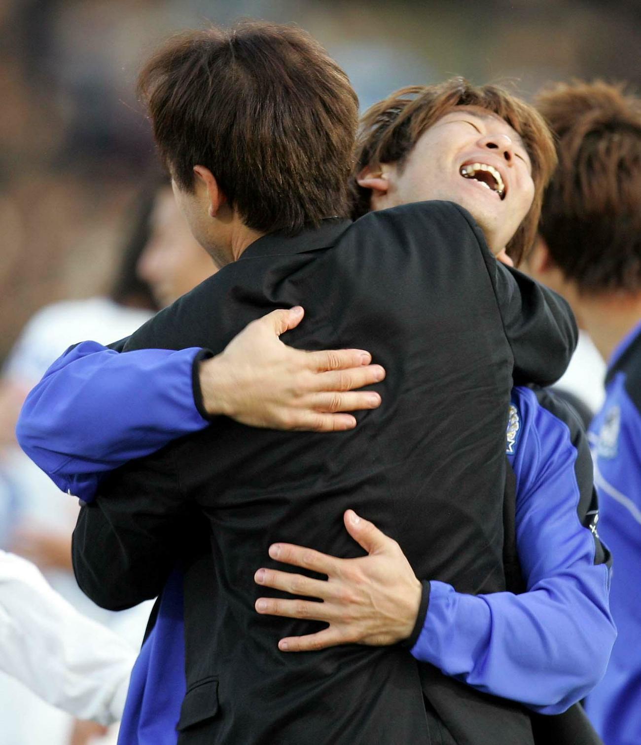 G大阪が初優勝し、西野朗監督と抱き合って喜ぶ大黒将志(2005年12月3日撮影)