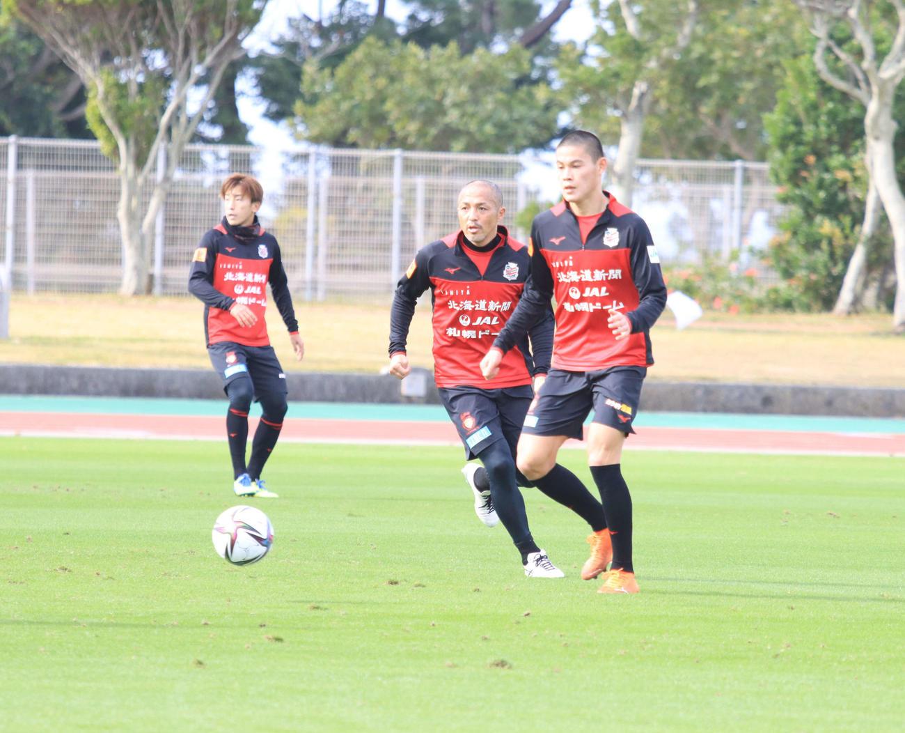 沖縄キャンプの午前練習、ボールを追う札幌MF小野(中央)。右はFW中島(撮影・保坂果那)