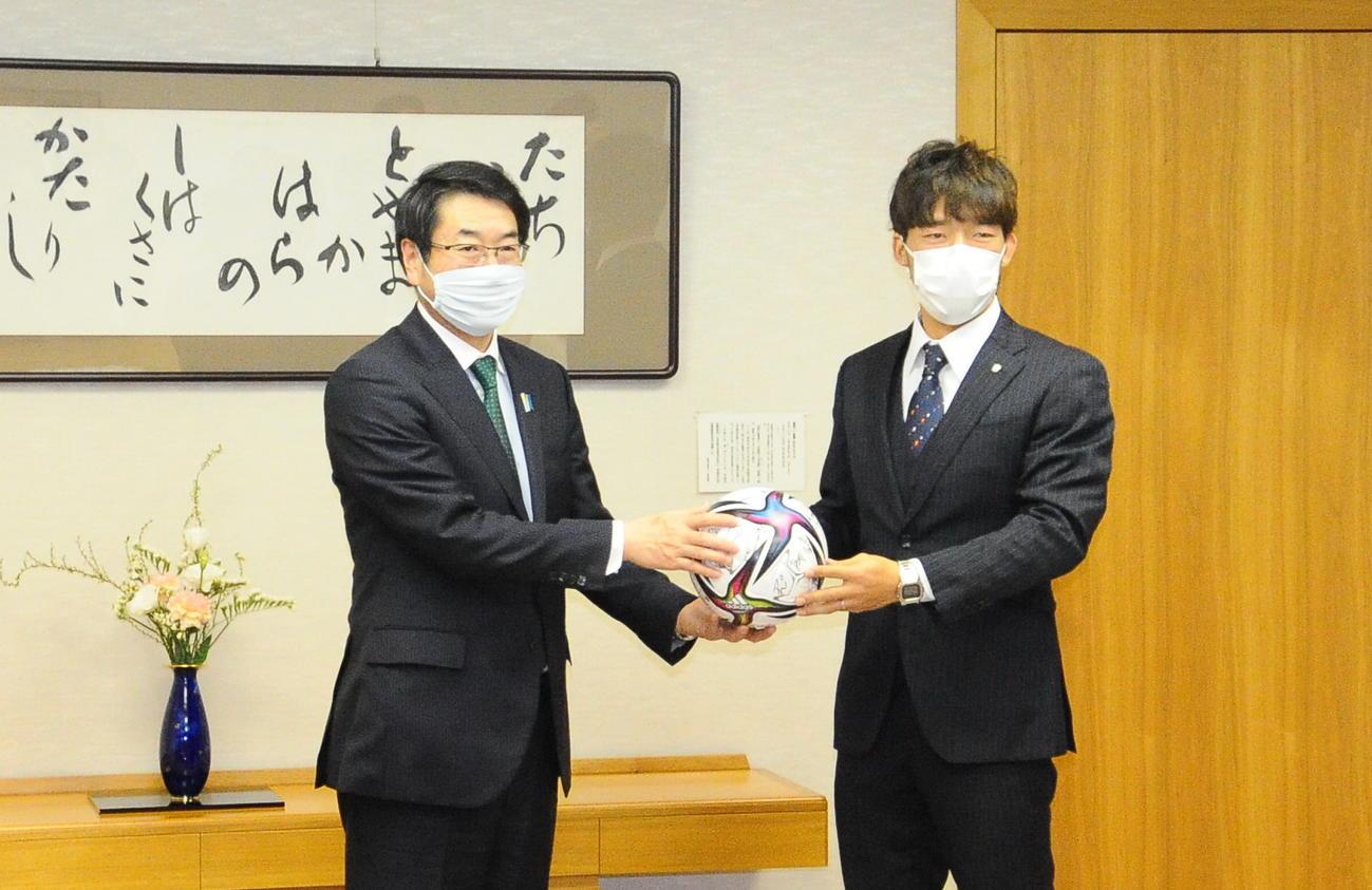 選手のサイン入りボールを新潟市の中原市長に渡す新潟鈴木(右)