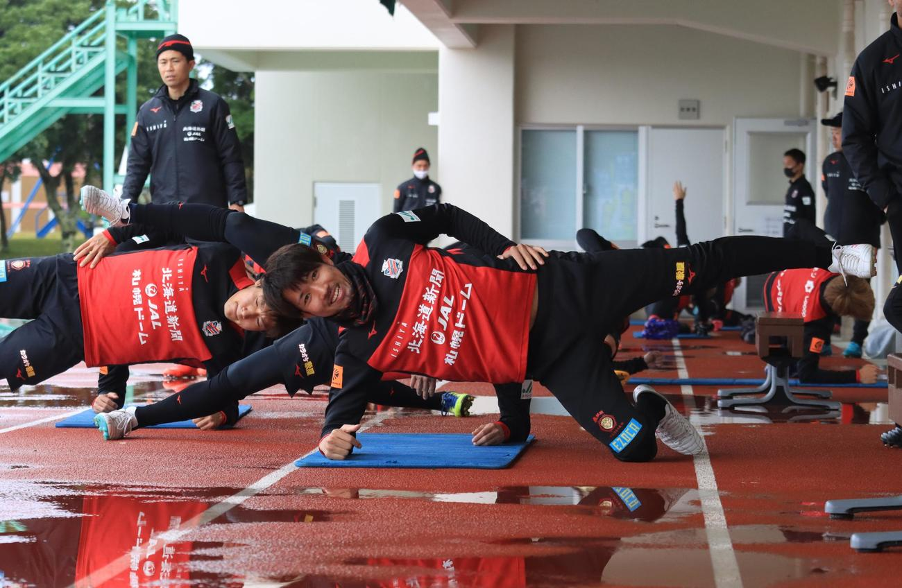 体幹トレーニング中にカメラに笑顔を見せる札幌DF柳(撮影・保坂果那)