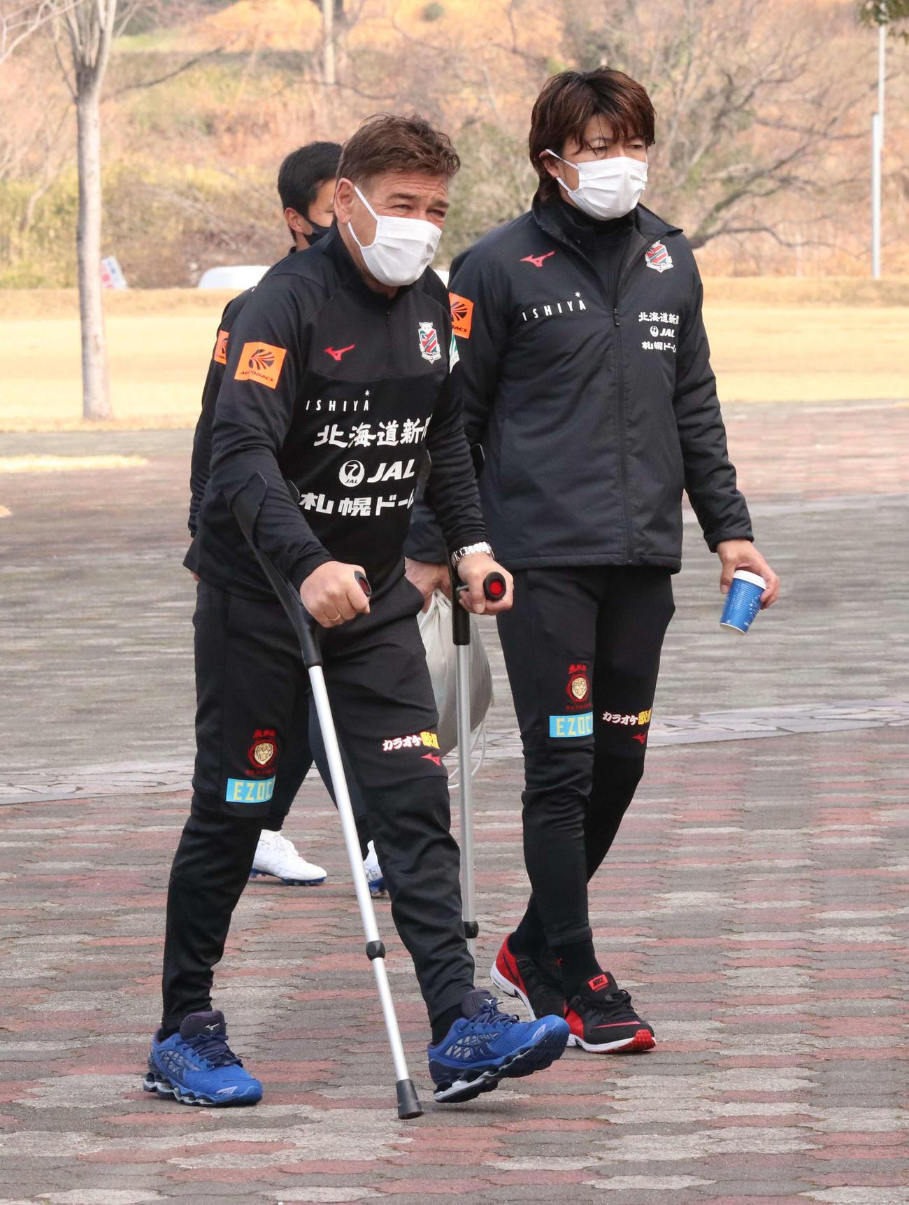 松葉づえ姿ながら元気な足取りでチーム活動に合流した札幌ペトロビッチ監督(左)(撮影・浅水友輝)