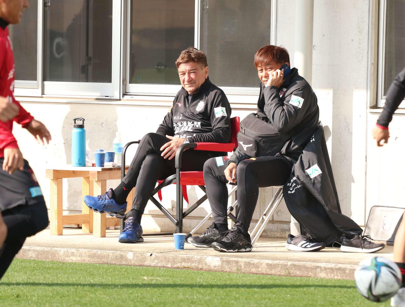 札幌ペトロビッチ監督(左)は三上GMと談笑しながら練習を見つめる(撮影・浅水友輝)