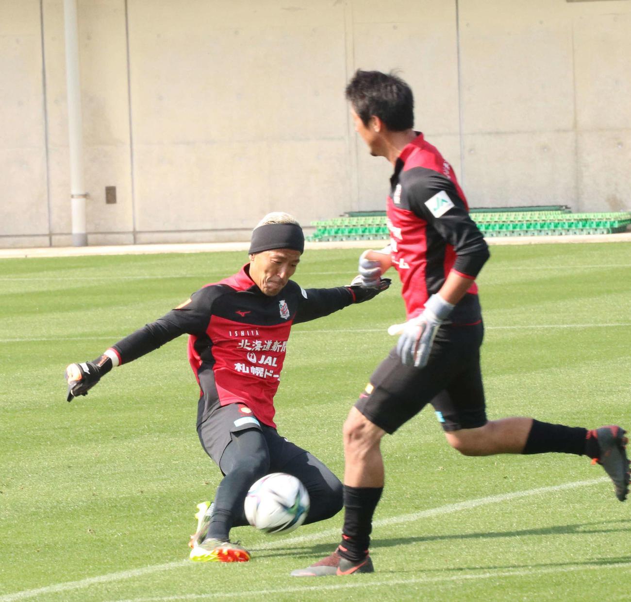 キーパー練習でボールを蹴る札幌GK菅野(左)(撮影・浅水友輝)