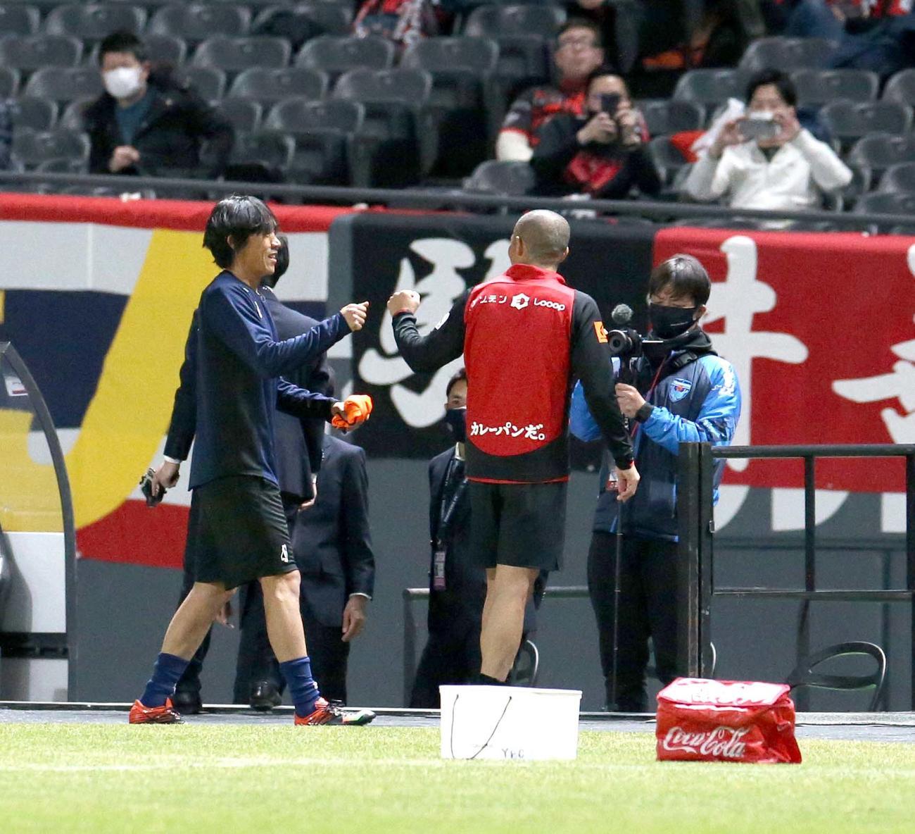 試合前、グータッチを交わす横浜FCのMF中村(左)と札幌MF小野(撮影・佐藤翔太)
