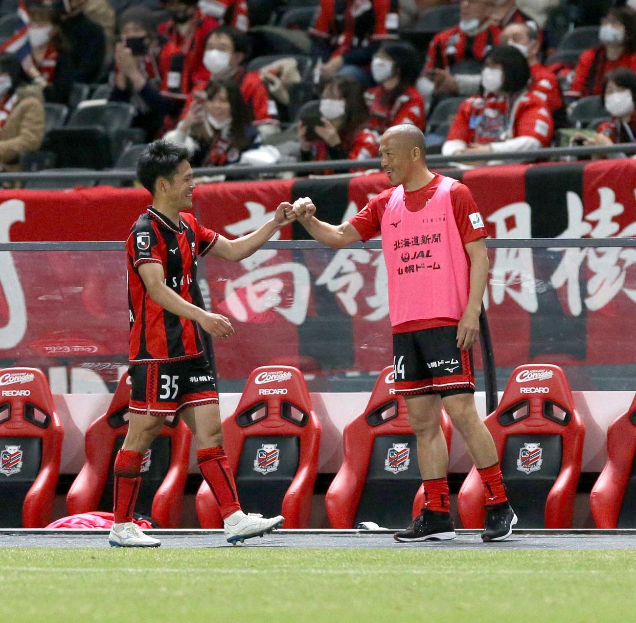 札幌対横浜FC ベンチ前でグータッチを交わす札幌FW小柏(左)とMF小野(撮影・佐藤翔太)