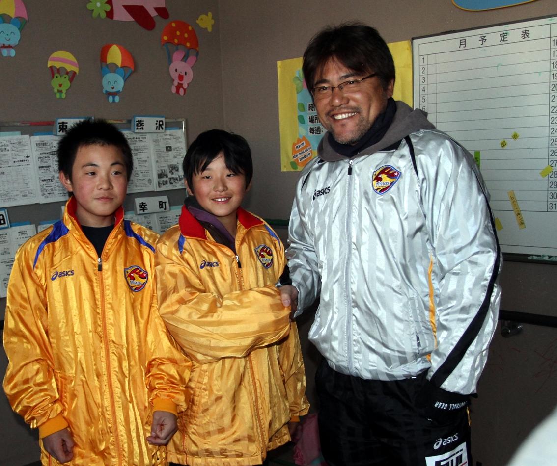 11年3月、仙台。手倉森監督(右)はモデルチェンジ前の旧チームジャージーなどを避難所の子どもら届けて激励する