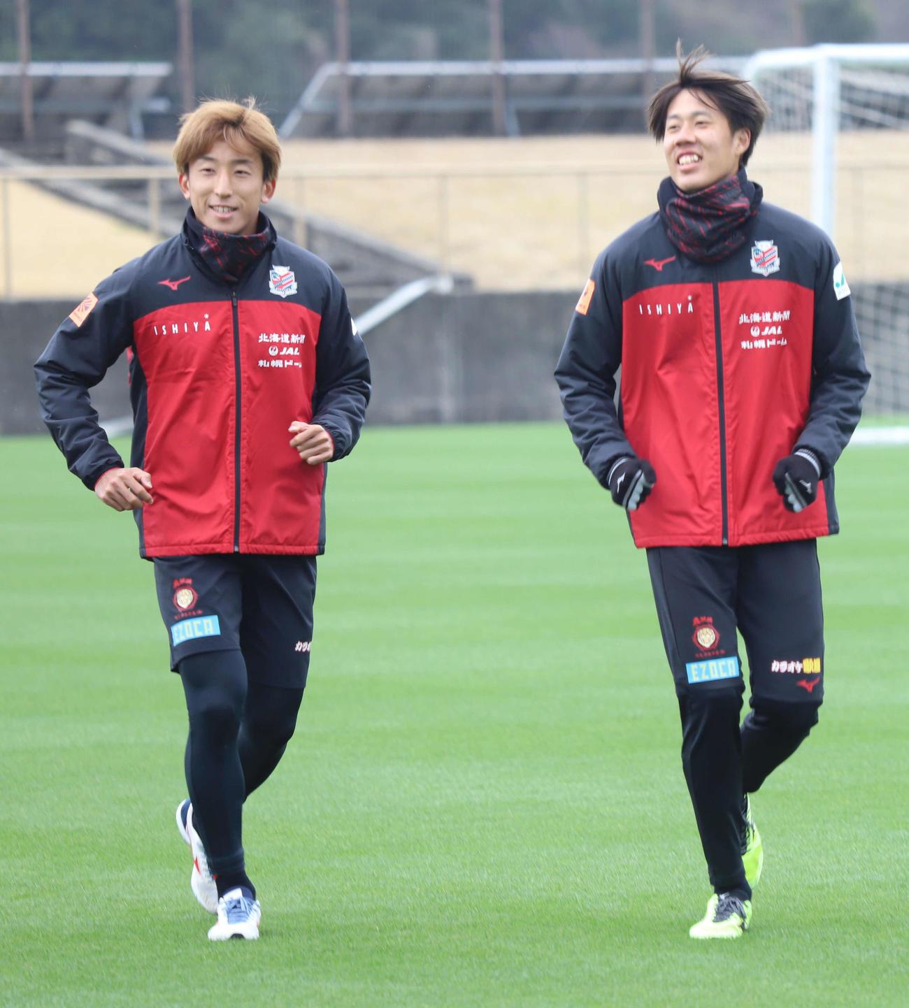 笑顔でランニングする札幌DF田中(右)。左はMF金子(c)2021 CONSADOLE