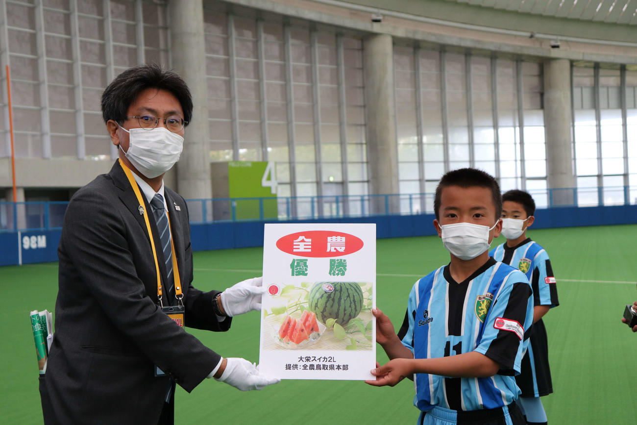 優勝チームに副賞目録を手渡すJA全農広報・調査部の沢登幸徳次長(左)