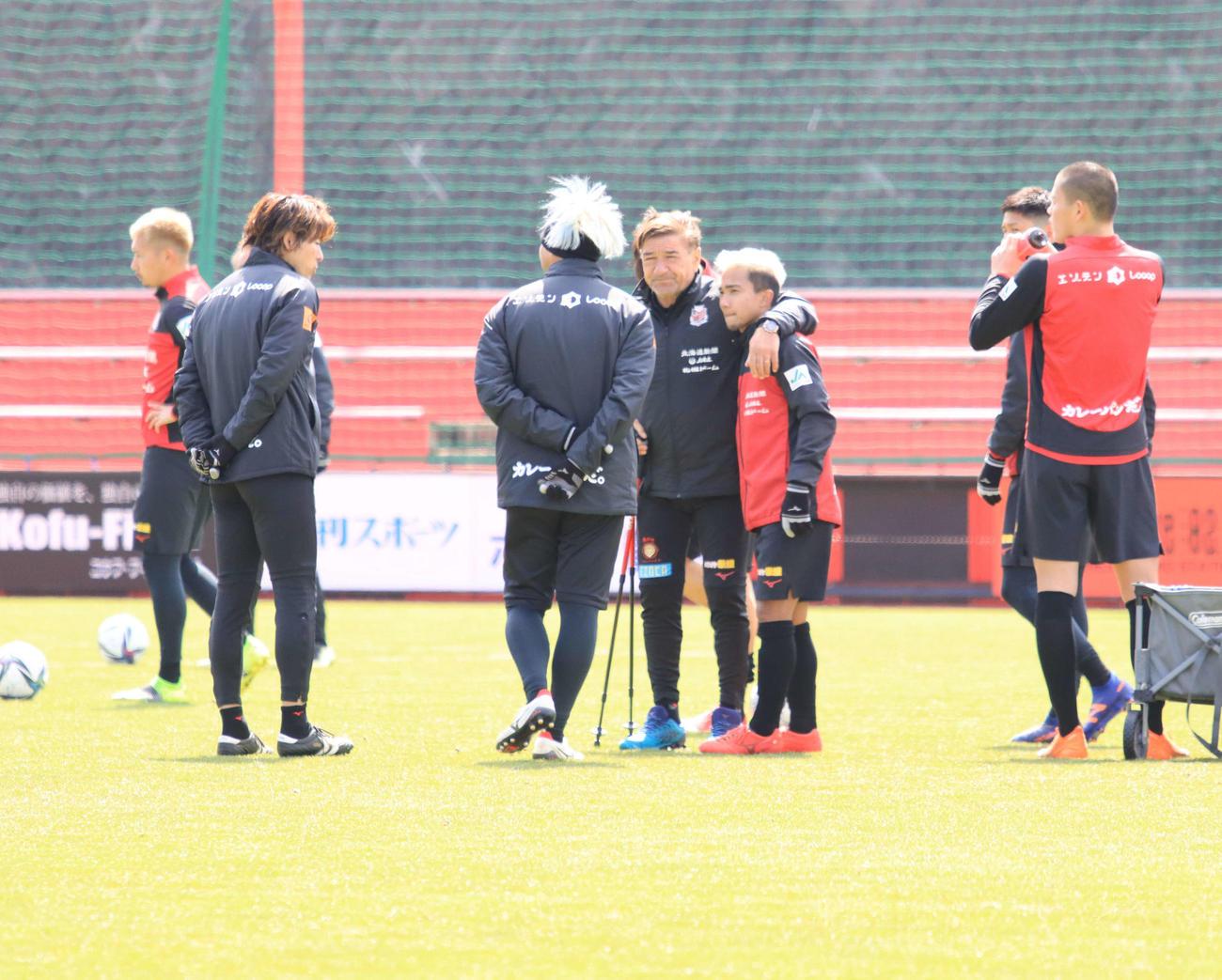 練習を終え、札幌MFチャナティップ(左から5人目)の肩を抱くペトロビッチ監督(同4人目)(撮影・保坂果那)