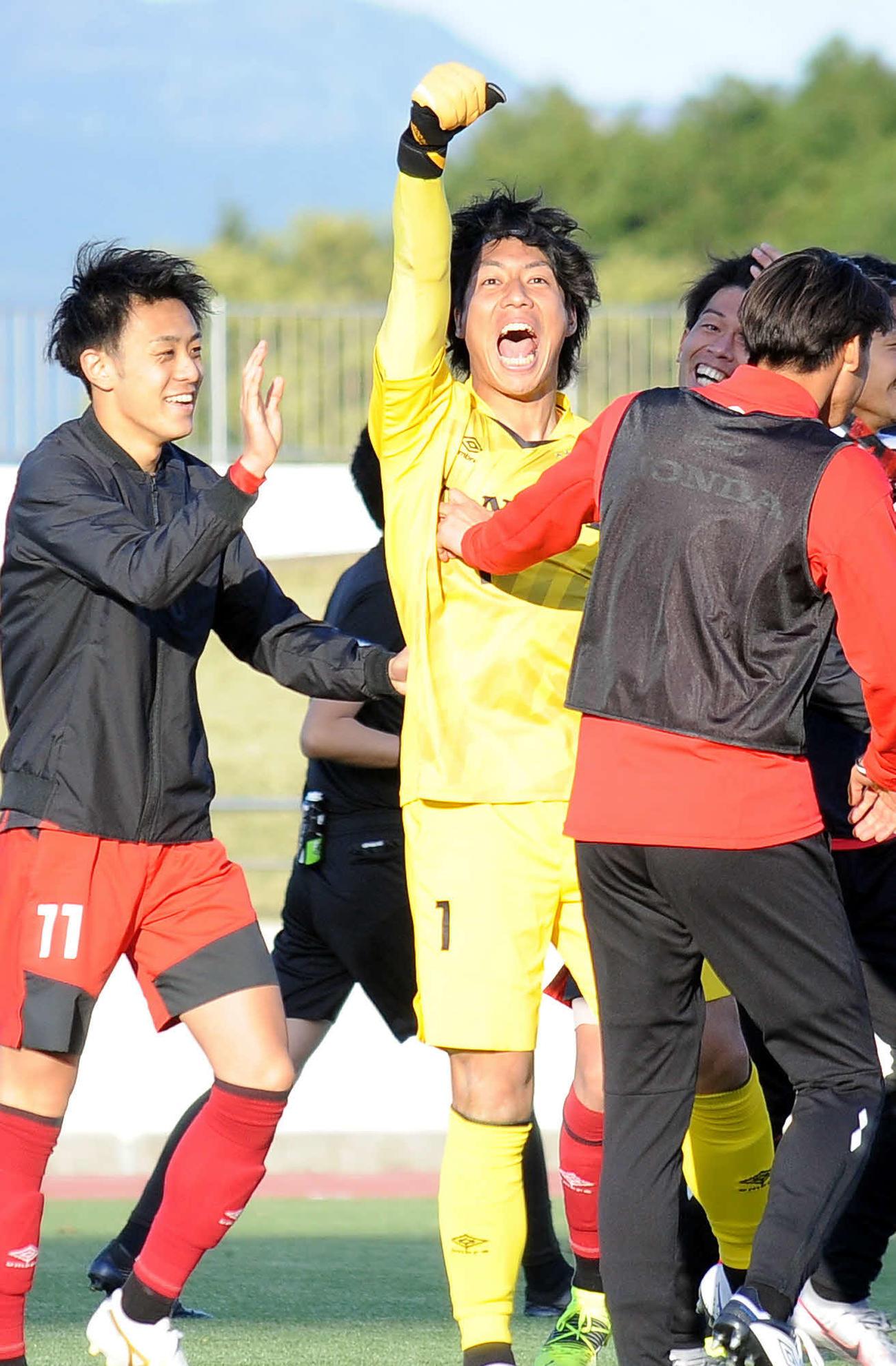 試合後、スタンドに向かってガッツポーズをするホンダFCのGK楠本(中央)