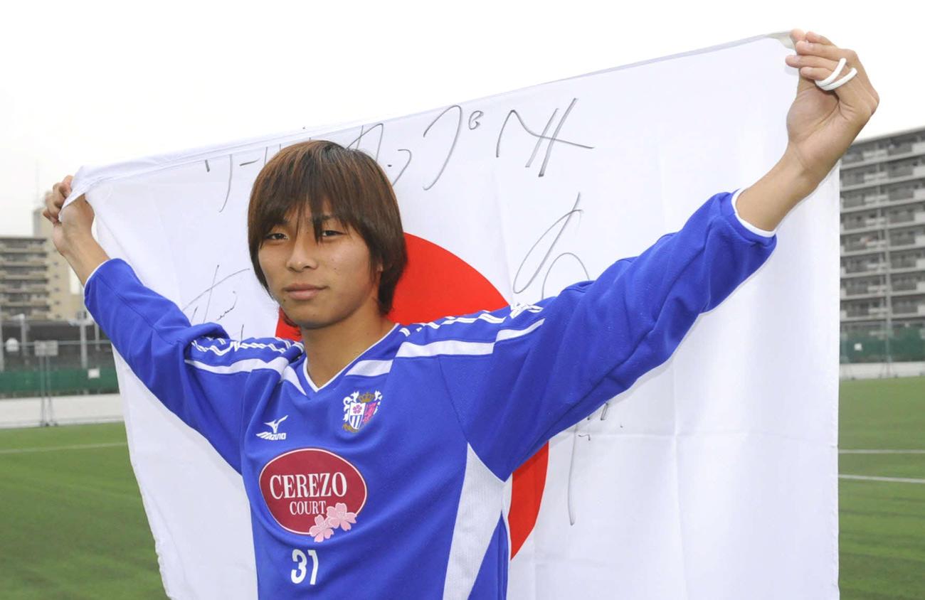 日本代表候補に選ばれ日の丸の旗を両手に掲げるC大阪時代の乾貴士(2008年12月24日撮影)