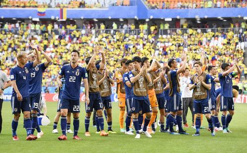 コロンビアに勝利し、サポーターの歓声に応える本田(左端)ら日本イレブン(共同)