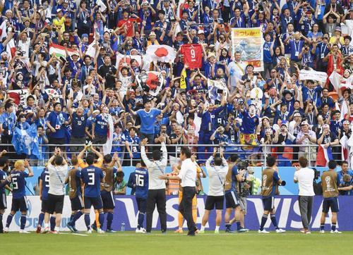 コロンビアに勝利した日本イレブン(手前)と喜ぶスタンドのサポーター(共同)