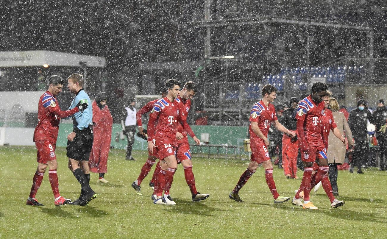 雪の中、肩を落として引き揚げるBミュンヘンの選手たち(ロイター)