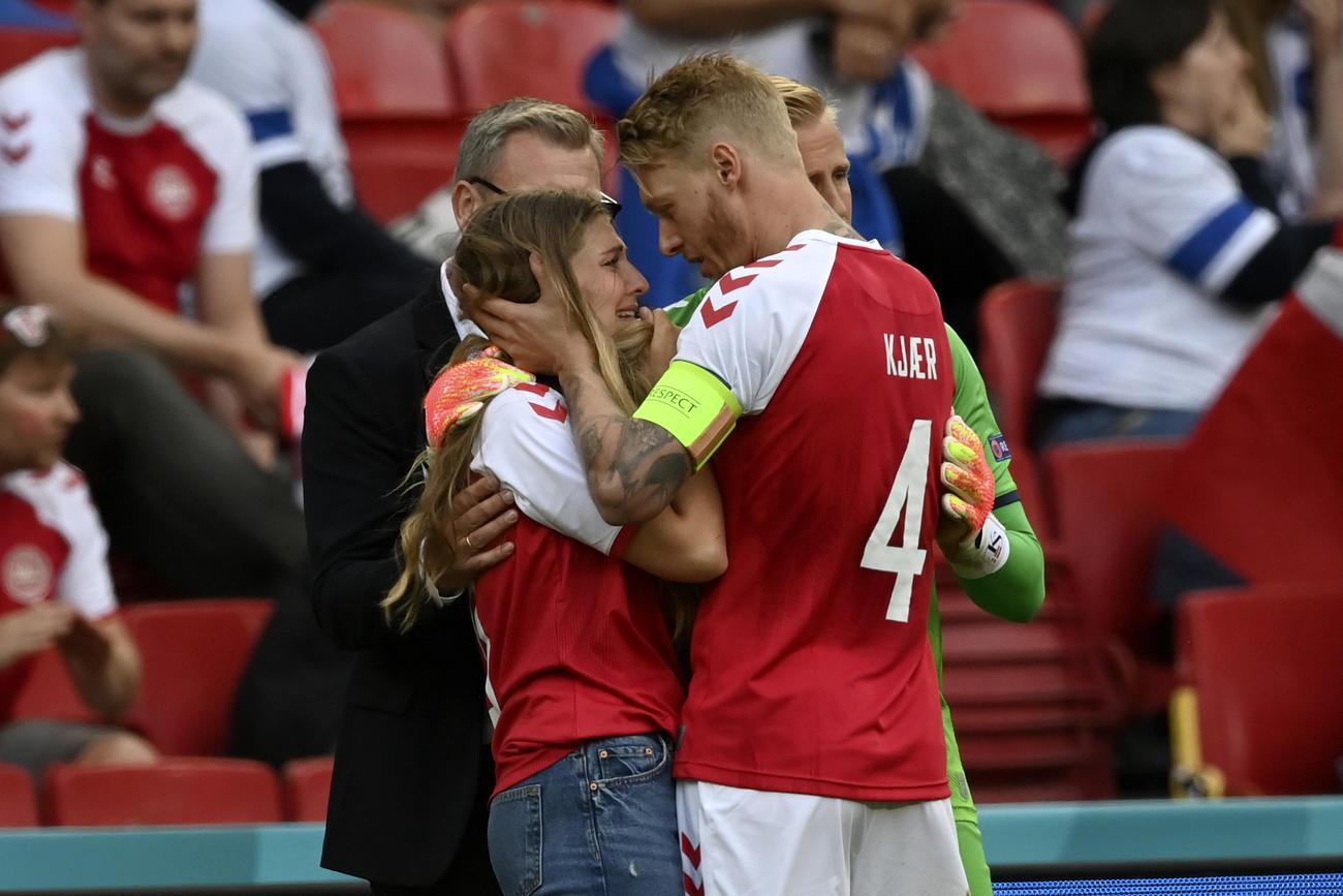 ピッチまで降りてきたエリクセンの妻サブリナさんを抱き留めるデンマークのケラー主将(AP)