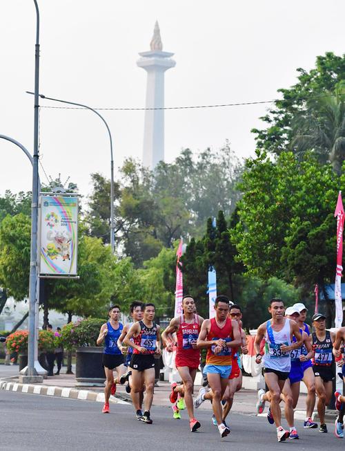 男子マラソン 中央ジャカルタ地区にあるモナス(独立記念塔)の前を通過する井上(左)と園田(撮影・清水貴仁)