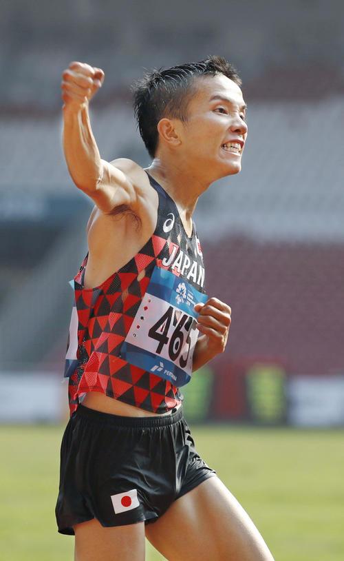 男子マラソンで優勝し、ガッツポーズする井上大仁(共同)
