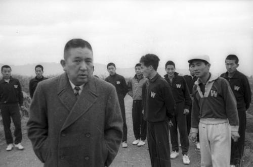 第35回大会 最終合宿で河野一郎監督(左)の話を聞く早大の選手たち(1958年12月23日)
