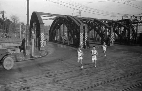 第24回大会 往路1区 品川・八ツ山橋を渡った左から中大・浅倉茂、東体専・伊東春雄、法大・池田弘文(1948年1月6日)