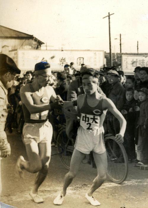第25回大会 往路2区鶴見中継所 1区浅倉茂(左)から2位でタスキを渡される中大2区井上俊一(右)(1949年1月5日)