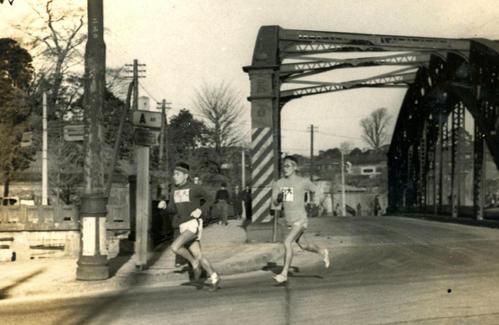 第25回大会 往路1区 八ツ山橋を渡りトップ争いをする明大・島村和男(左=区間1位)と中大・浅倉茂(右=区間2位)(1949年1月5日)
