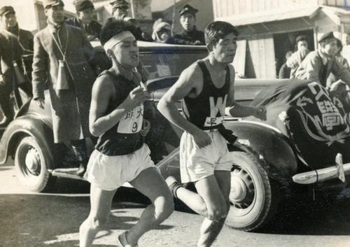 第25回大会 復路9区 横浜駅付近でついに追いついた早大・小林莞爾(右)は明大・安田正(左)と生麦ガード付近を並走(1949年1月6日)