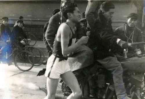 第25回大会 復路10区 1度はトップに立った早大アンカー水野栄英だったが、明大の追い上げにあい左脚のケイレンをおこし苦悶の表情(1949年1月6日)