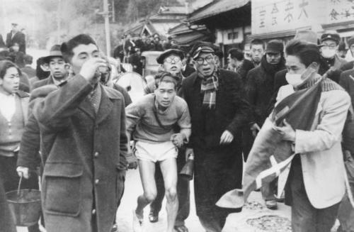 第25回大会 往路5区 ゴール前残り200メートル辺りで倒れた中大・西田勝雄(中)は関係者の手を借りゴールまで歩く。※選手に触れることは規則違反だが、審判長が認めたため役員会で改めて判定(1949年1月5日)