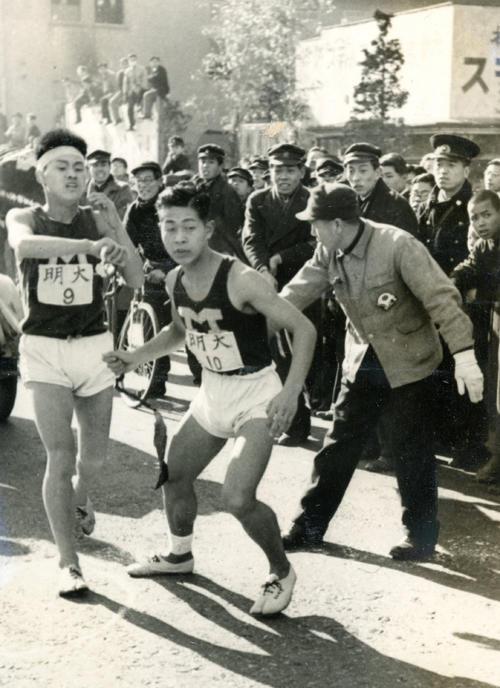 第25回大会 復路10区 鶴見中継所手前で猛然とスパートした明大9区安田正(左)は、早大に27秒差でアンカー木渓博志(右)にタスキリレー(1949年1月6日)