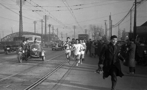第27回大会 往路1区 八ツ山橋を渡り第一京浜でトップ争いをする日大・種村幸夫(左=区間2位)と神奈川大・三橋兼信(右=区間6位)(1951年1月5日)