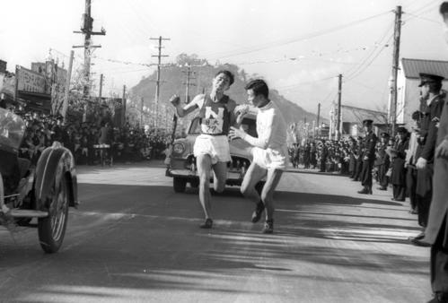 第31回大会 復路8区平塚中継所 2位の日大は7区山岸実(左)から8区馬場英則(右)へタスキリレー(1955年1月3日)