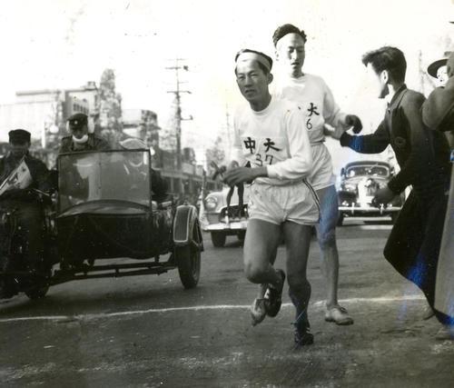 第31回大会 復路7区小田原中継所 6区西村良三(後方)からトップでタスキをもらった中大7区布上正之(手前)(1955年1月3日)