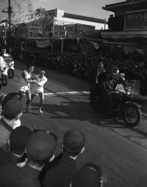 第31回大会 5区小田原中継所 4区吉田斉(左)から5区谷敷正雄へトップでタスキをつなぐ中大(1955年1月2日)