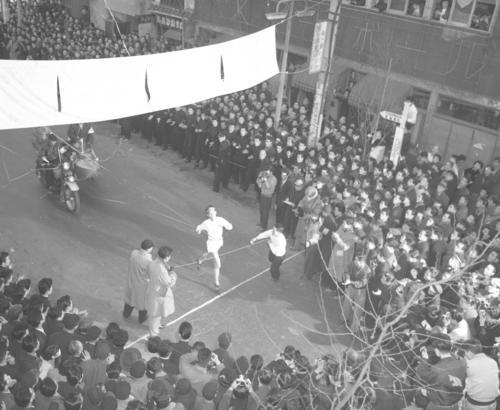 第32回大会 復路10区読売新聞社横ゴール 2年連続7度目の優勝テープを切る中大のアンカー布上正之。総合12時間4分49秒、復路5時間58分11秒(復路新)(1956年1月3日)