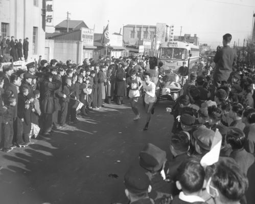 第32回大会 往路2区 トップの法大・山内二郎(左)は、1時間9分47秒の区間新で2区鯉川司(右)にタスキを渡す(1956年1月2日)