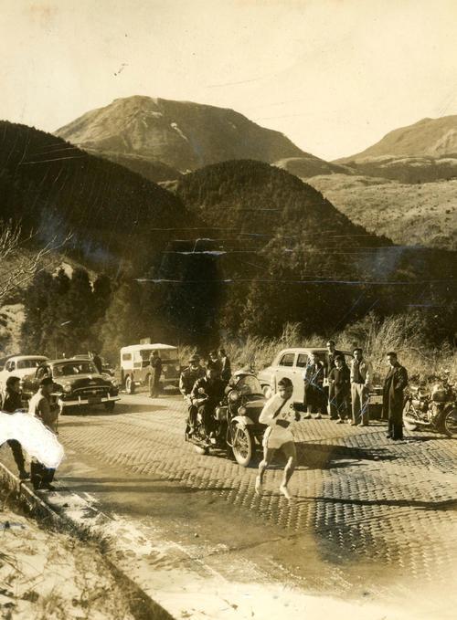 第32回大会 往路5区 タスキを受けて間もなく板橋付近で1度は日大・内川義高に抜かれた中大・谷敷正雄だったが、無理な急追の内川を抜き返し箱根七曲りの上りを力走。後方は駒ケ岳(1956年1月2日)