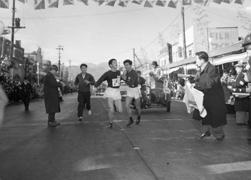 第33回大会 復路7区 トップ日大は最後へばった6区島田武之(左)から7区横山和五郎(右)へタスキが渡る(1957年1月3日)