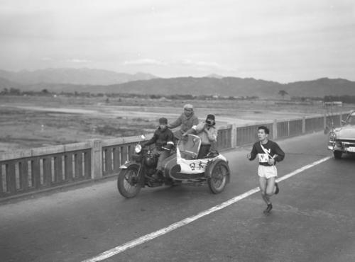 第33回大会 往路4区 サイドカーからの激励を受けピッチを上げるトップを行く日大・松川行毎(1957年1月2日)