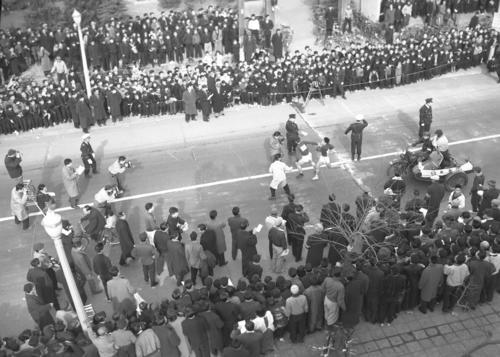 第33回大会 往路4区平塚中継所 トップ日大は3区瀬戸功夫(右)から4区松川行毎(左)にタスキが渡る(1957年1月2日)