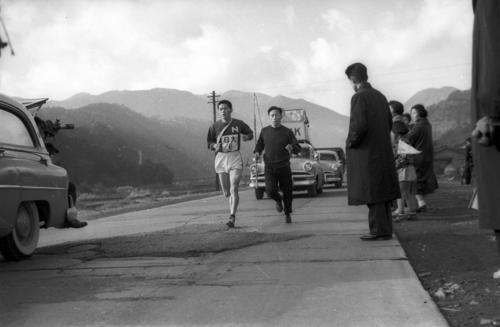第34回大会 復路6区 中大に13分8秒差で往路優勝した日大は、連覇へ向け島田武之(左=3年)が山下りを終え湯本から小田原中継所へ向かう(1958年1月3日)